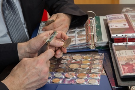 51354986 - two numismatists examines  collection of coin
